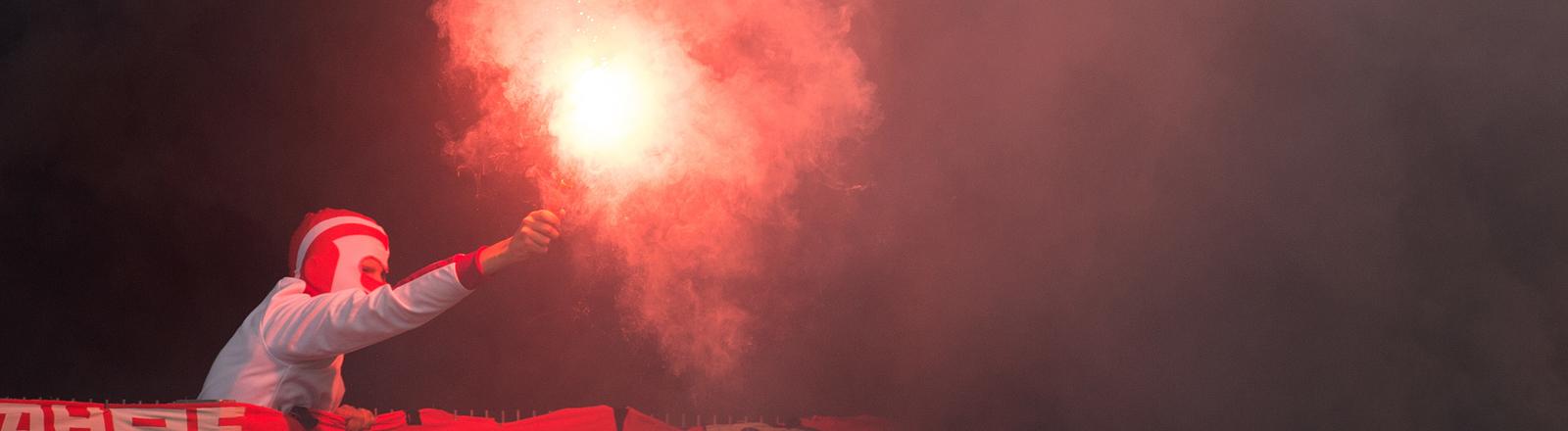 Mann mit bengalischen Feuer im Stadion
