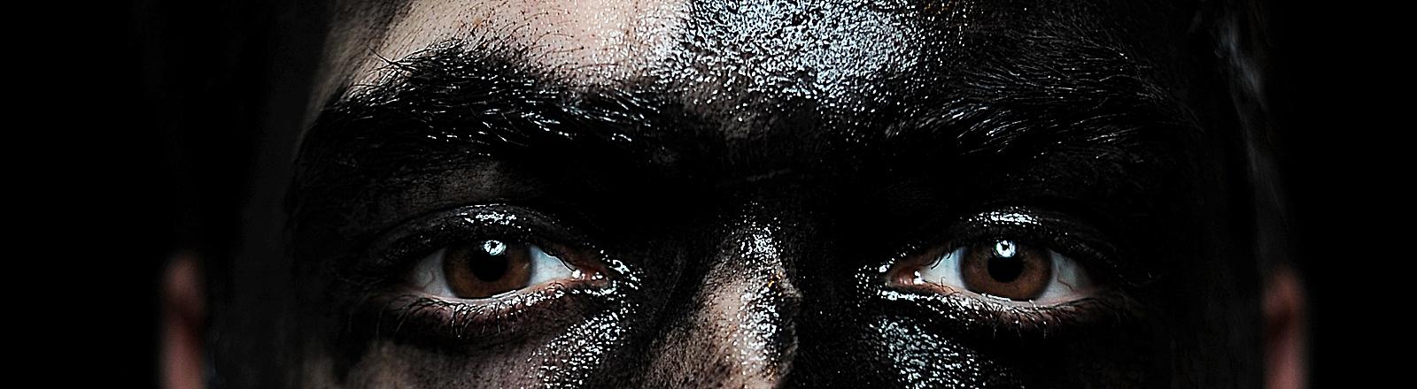 Mann mit verwischter schwarzer Farbe im Gesicht