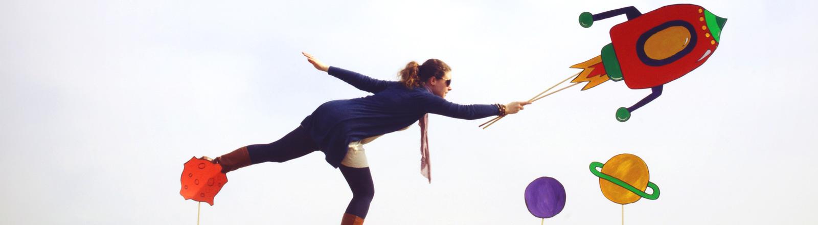 Eine Frau steht auf einem Bein und wird von einer Rakete gezogen.