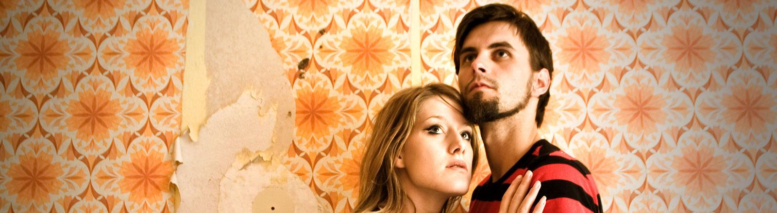 Ein Paar steht vor einer Tapete und schmiegt sich aneinander.