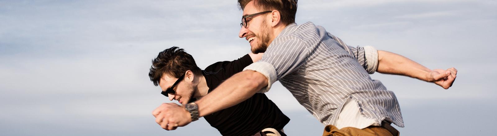 Zwei Männer springen am Strand in die Luft