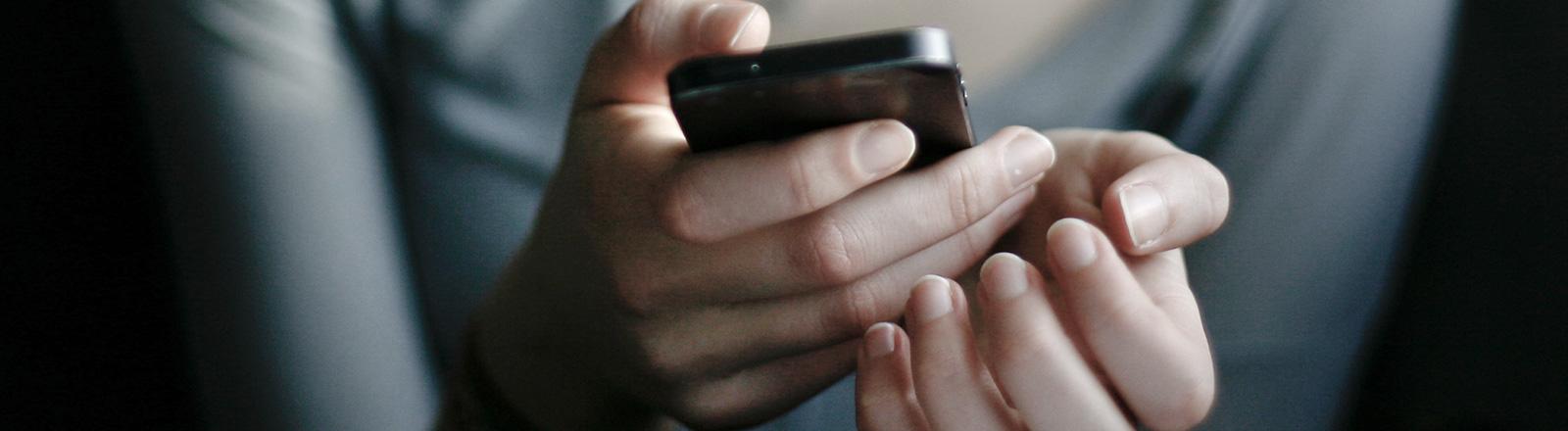 Zwei Hände, die ein Smartphone halten.