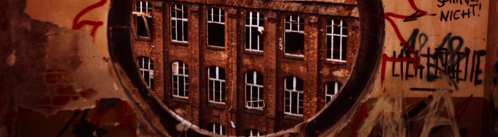 Ein alter Fabrikgebäude gesehen durch ein Guckloch.