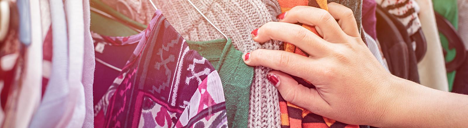 Kleiderschrank: Hände ziehen Klamotten auf Kleiderbügeln heraus.