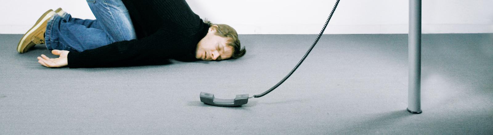 Schlafender Mann vor einem Schreibtisch