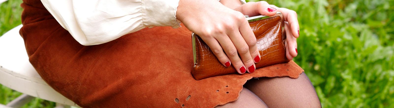 Frau hält ihr Portemonnaie in der Hand