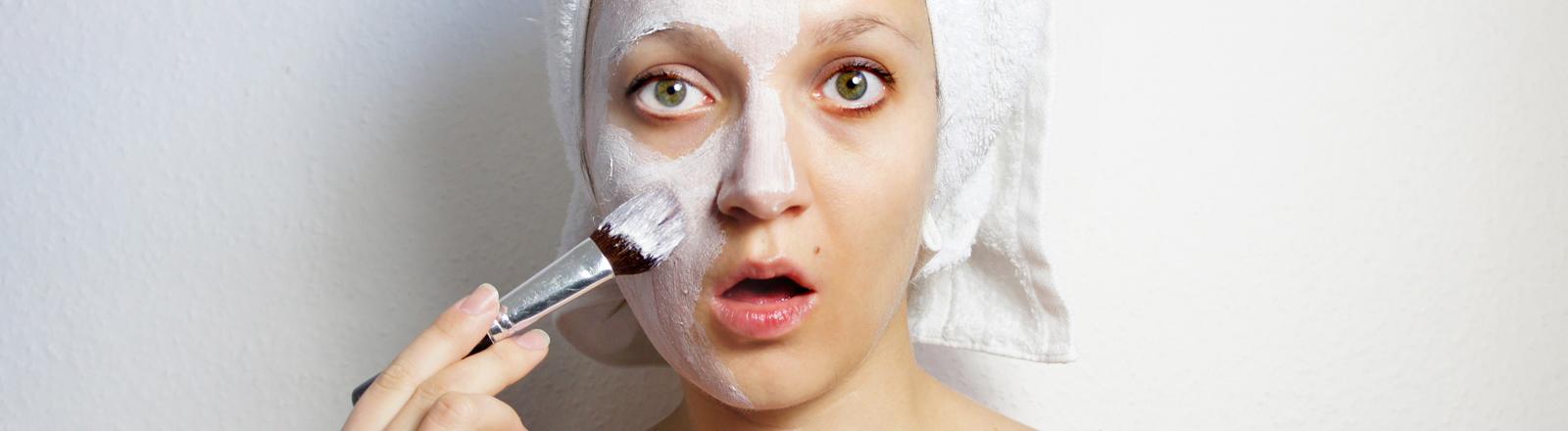 Frau mit Gesichtsmaske mit Pinsel