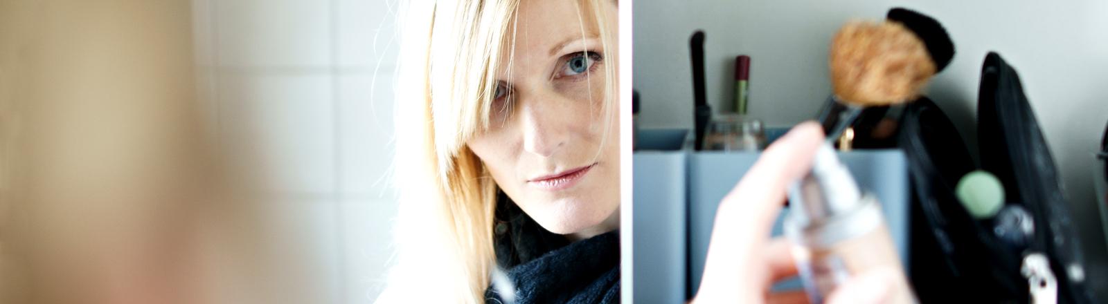 Frau blickt in geöffneten Kosmetikschrank