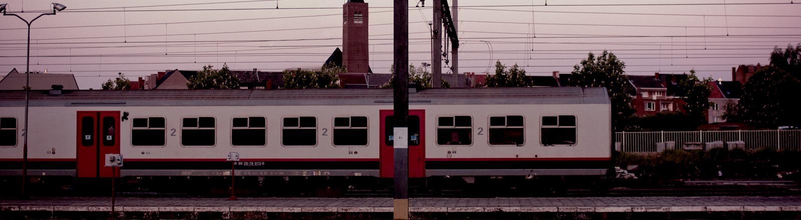 Ein Bahnhof, am Gleis steht ein Zug.
