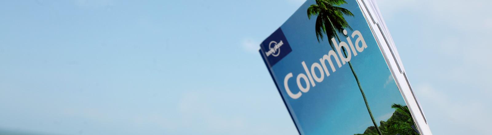 Eine junge Frau liest im Lonely Planet Columbia am Strand der kolumbianischen Karibikkueste.
