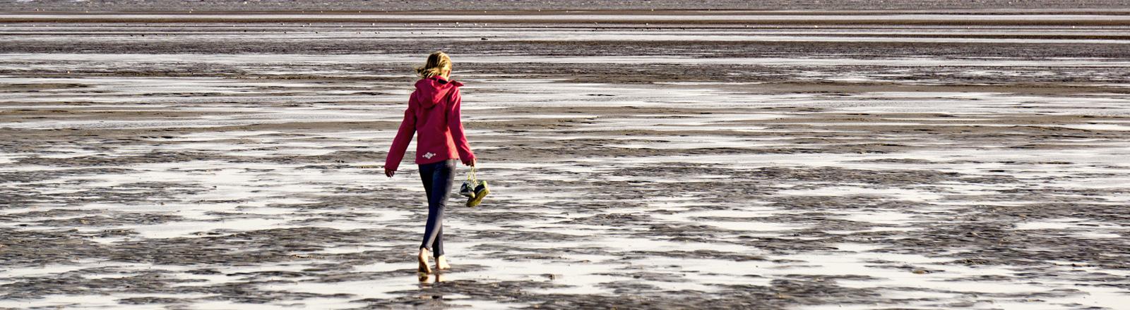 Eine Frau geht durchs Watt mit nackten Füßen.