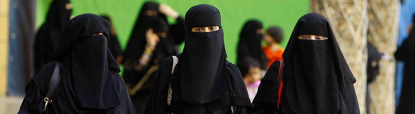 Drei saudi-arabische Frauen mit einem Ganzkörperschleier.
