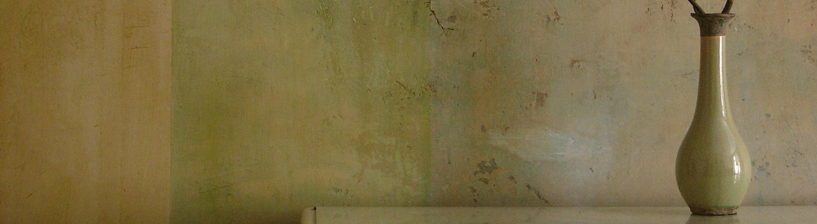 Eine Vase steht auf einer Anrichte vor einer Wand in einer Altbauwohnung.