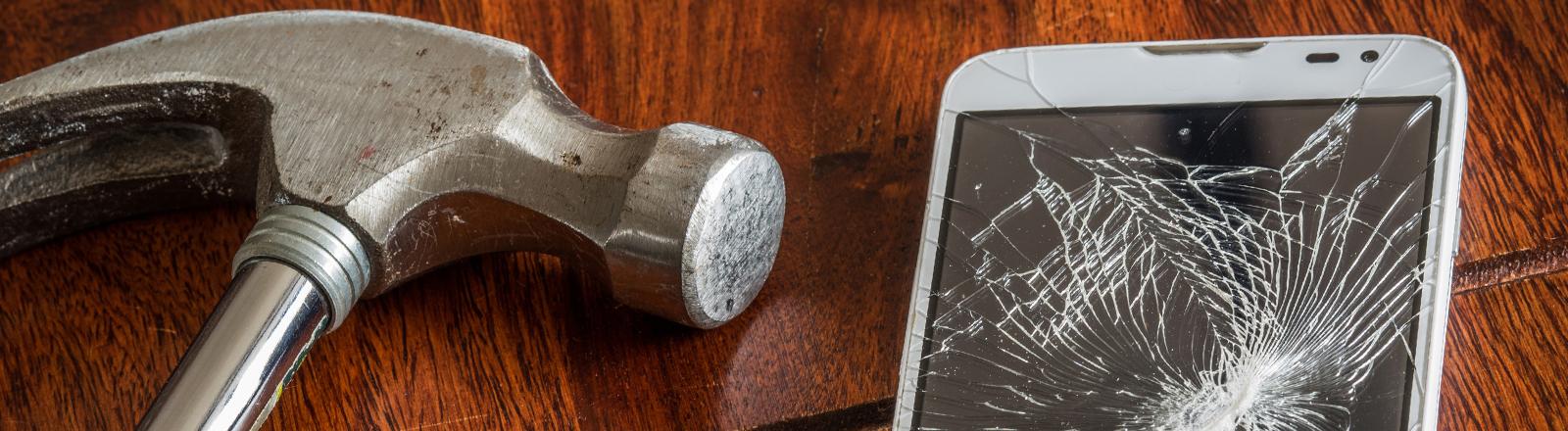 Smartphone mit defektem Display neben Hammer