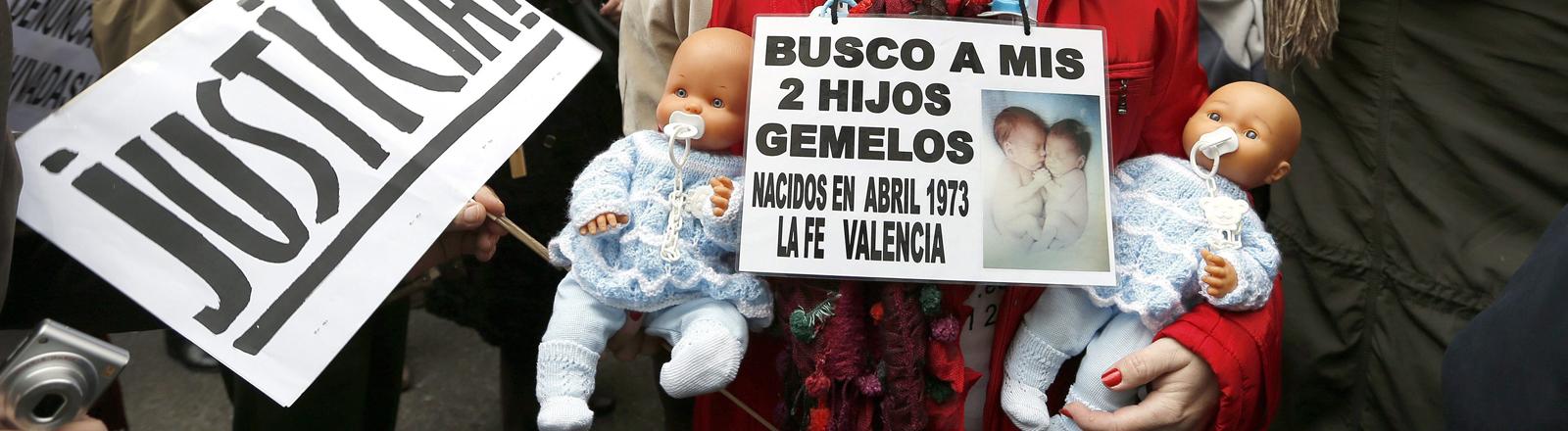Frau mit zwei Puppen im Arm. Ein Schild baumelt vor ihrer Brust: Suche meine zwei Söhne. Zwillinge, geboren im April 1973.