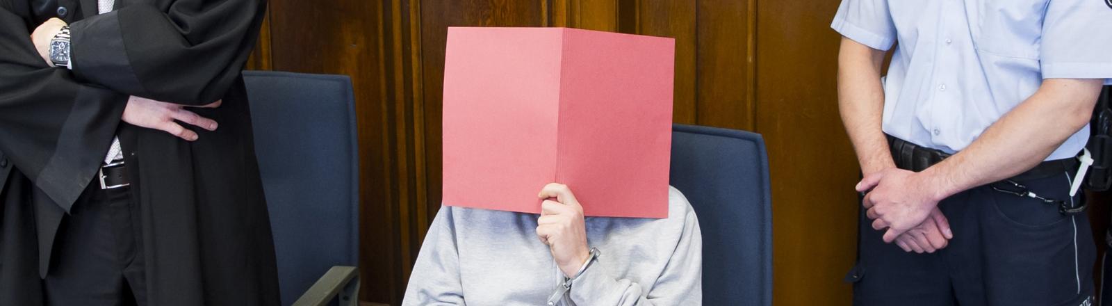Ein Angeklagter wegen sexueller Übergriffe vor Gericht hält sich eine rote Mappe vor das Gesicht.