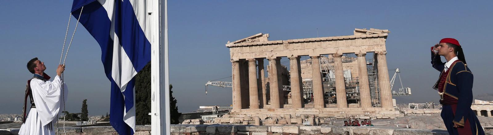 die griechische Flagge wird gehisst. Im Hintergrund: Die Akropolis