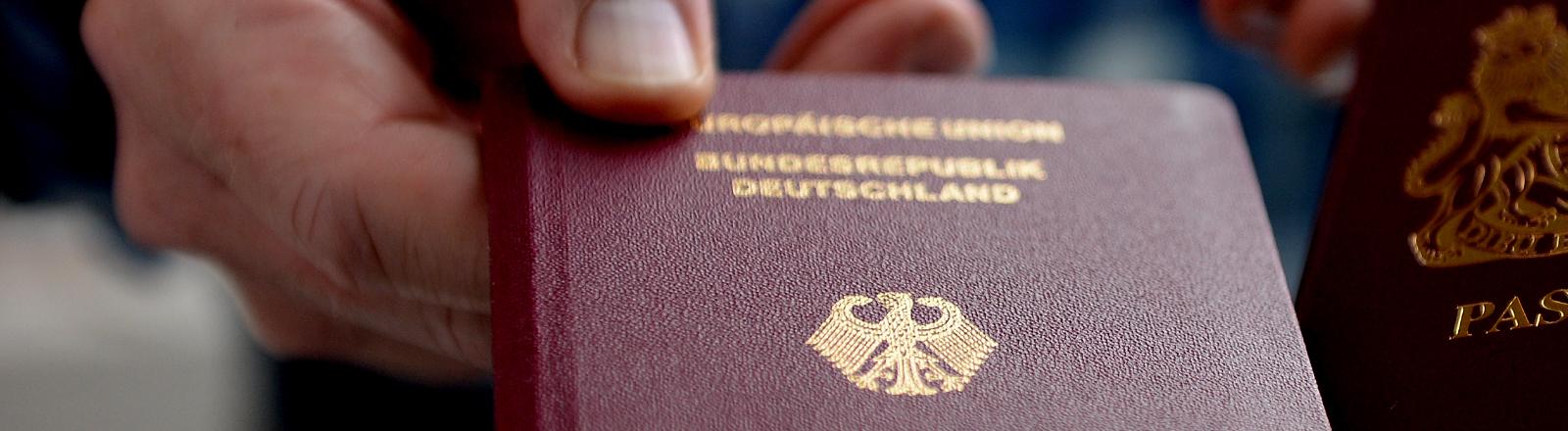 Eine Person hält einen deutschen Reisepass in der Hand.