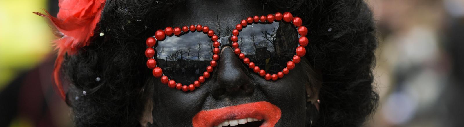 Schwarz geschminkte Frau mit roten Lippen und Herzchensonnenbrille.