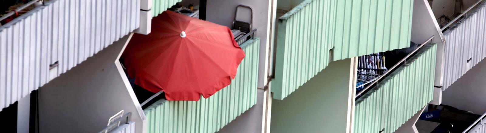 Blick von oben auf Balkone - auf einem steht ein roter Sonnenschirm.