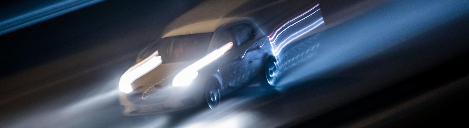 Ein Auto bei Nacht mit Schweinwerferlicht, verschwommen