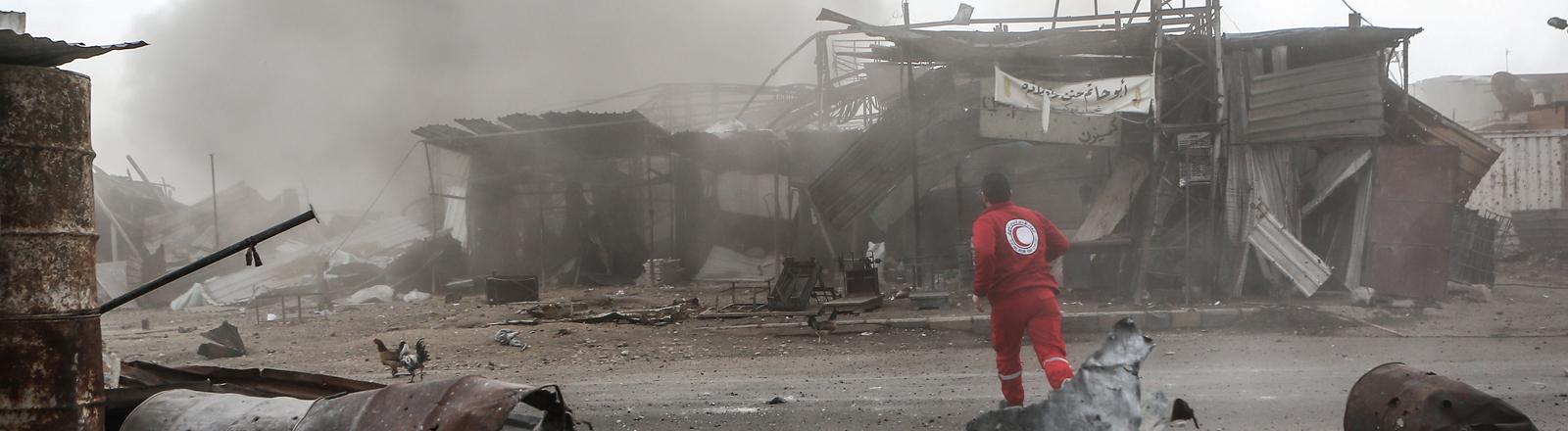 20.02.2018, Syrien, Duma: Ein Mitarbeiter der Organisation Syrischer Roter Halbmond geht durch ein Viertel der Stadt im syrischen Rebellengebiet Ost-Ghuta nahe Damaskus, das von Angriffen der syrischen Luftwaffe getroffen wurde.
