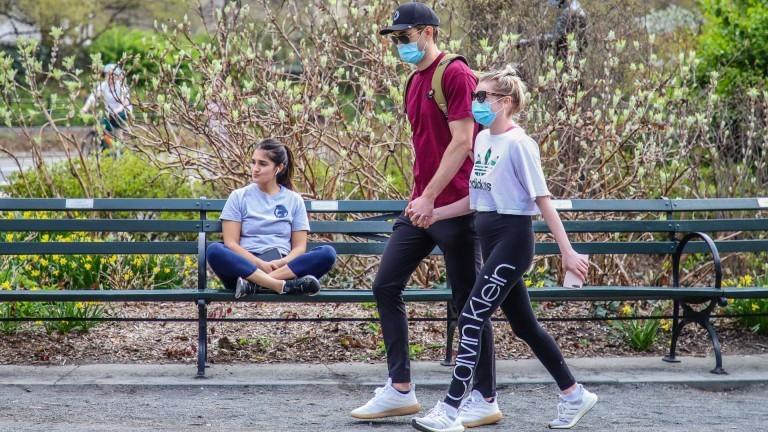 Ein Paar mit Mundschutz läuft Hand in Hand im T-Shirt durch einen Park. Auf einer Bank sitzt eine junge Frau - ebenfalls im T-Shirt.