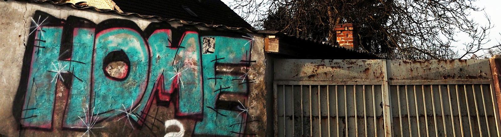 Graffiti Home auf einer Gartenmauer