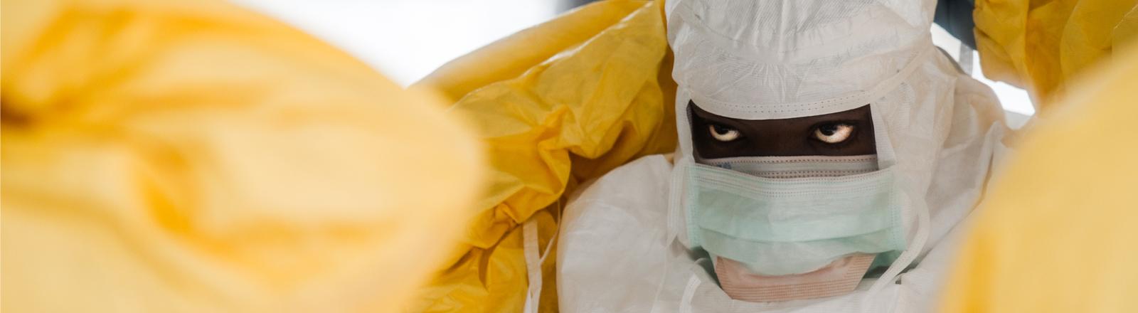 Ein Mann ist komplett in gelbe Schutzkleidung gekleidet. Er bindet sich eine Atemschutzmaske um.
