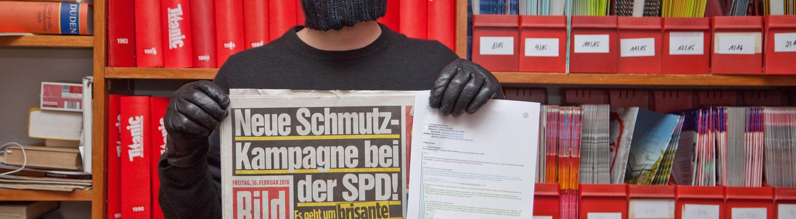 """Mitarbeiter des Satiremagazins Titanic, der die Bildzeitung vom Freitag den 16.2.2018 in den Händen hält. Der Redakteur trägt eine Sturmmaske und schwarze Handschuhe. Auf der Titelseite: """"Neue Schmutzkampagne bei der SPD"""""""