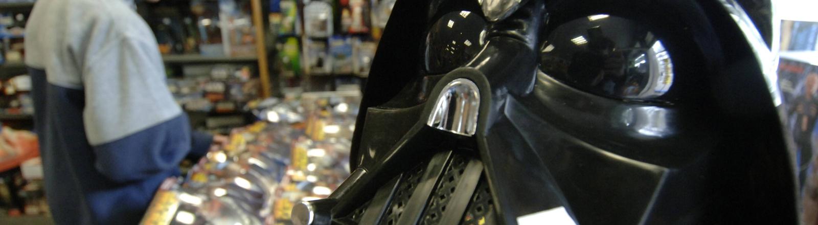 """Ein Kind schaut sich am Donnerstag (12.05.2005) in Hamburg in einem Fantasy-Shop hinter einem """"Darth Vader""""-Helm """"Star Wars""""-Figuren an."""