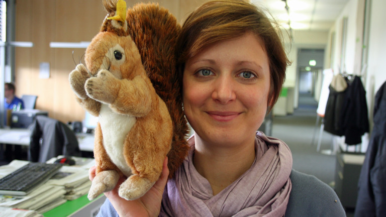 DRadio-Wissen-Redakteurin Julia präsentiert ihr Plüsch-Eichhörnchen in der Redaktion.
