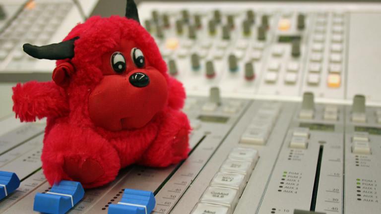 Ein roter Plüschteufel sitzt auf einem Mischpult in der DRadio-Wissen-Redaktion.