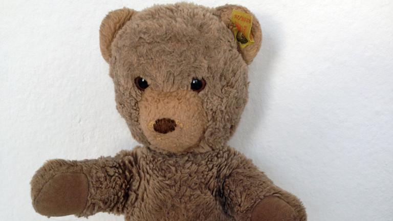 Ein Teddybär vor weißer Wand.