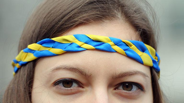 Einen Frau trägt am 02.03.2014 vor der russischen Botschaft in Berlin einen Kranz mit den Nationalfarben der Ukraine auf dem Kopf.