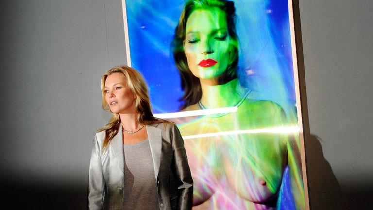 Topmodel Kate Moss bei einer Vernissage, hinter ihr sieht man eine künstlerisch bearbeitete Fotografie von ihr.