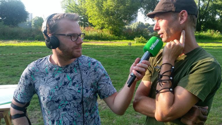 Christian Schmitt mit Mikrofon. Neben ihm steht Lars Christensen, er trägt grünes T-Shirt und eine braune Schirmmütze.