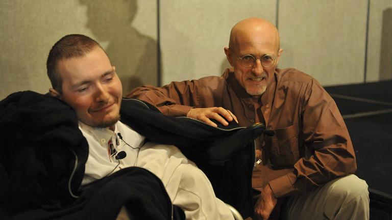 Waleri Spiridonow sitzt in einem Rollstuhl, er trägt ein weißes Hemd. Die Haare sind kurz. Neben ihm kniet der Chirurg Sergio Canavero.