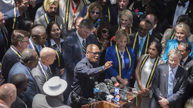 Der Polizeichef David Brown steht im Freien an einem Pult, auf dem viele Mikrofone liegen. Er spricht bei einer Gedenkfeier nach den Schüssen auf Polizisten in Dallas am 07.07.2016. Direkt um ihn herum stehen mehrere Männer und Frauen.
