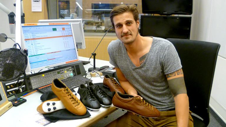 Markus Stolla, Entwickler eines Retro-Fußballschuhs, mit ein paar Schuhen im DRadio-Wissen-Studio