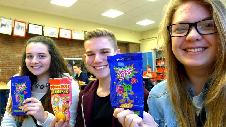 Drei Schüler einer neunten Klasse mit Süßigkeiten der 90er-Jahre.