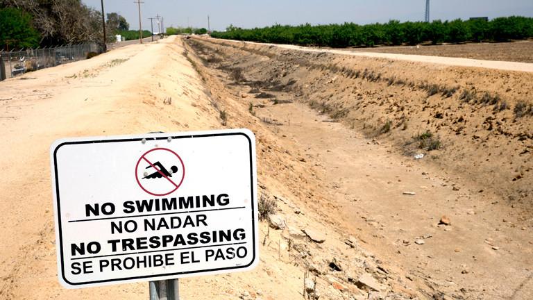 Ein Schild in Kalifornien, das das Schwimmen in einem Kanal verbietet.