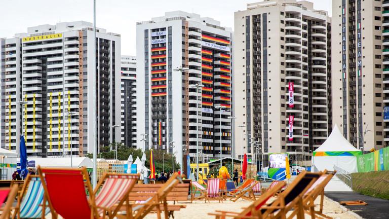 Das olympische Dorf in Rio, davor Liegestühle am Strand.