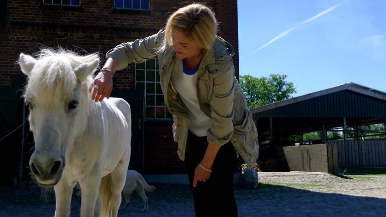 Anne Bente Isenberg streichelt ein Pferd.