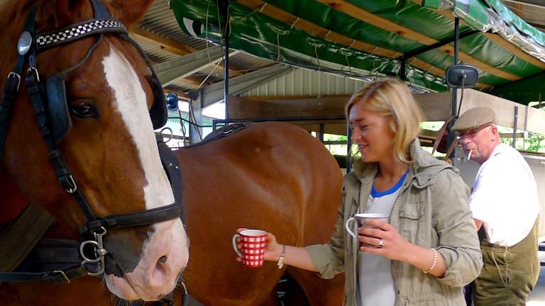 Anne Bente Isenburg mit zwei Tassen Kaffee vor einem Pferd.