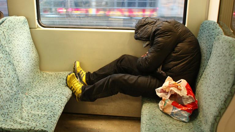 Ein Mann sitzt in einer S-Bahn und schläft.