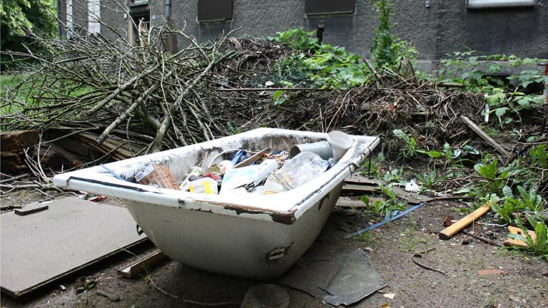 Eine alte Badewanne steht voller Müll im Hof.