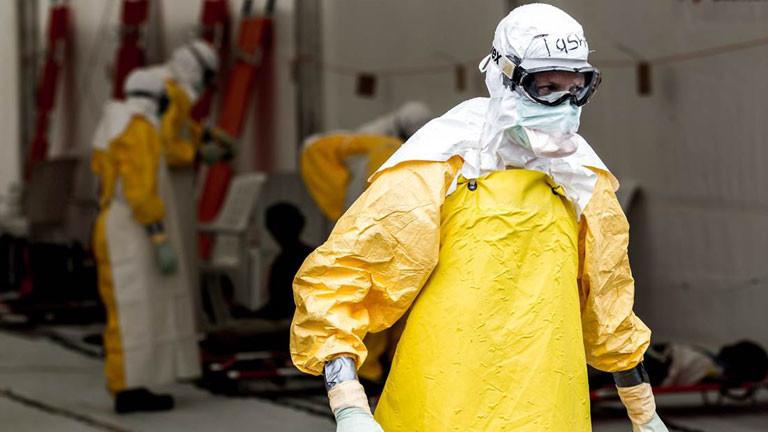 Eine Person ist komplett in Schutzkleidung gekleidet, um sich vor dem Ebolavirus zu schützen.