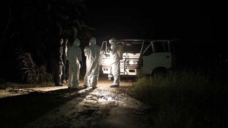 Ein Bestattungsteam in Liberia bereitet sich nachts darauf vor einen Ebolatoten aus einer Baracke zu holen.