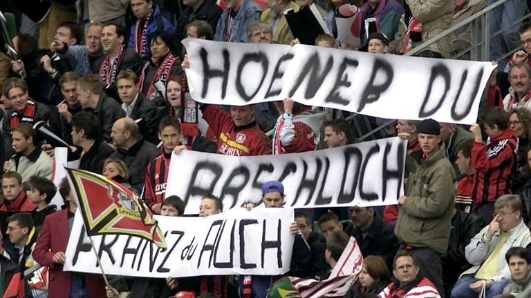 """Fans von Bayer 04 Leverkusen halten ein Transparent mit der Aufschrift """"Hoeneß Du Arschloch - FRanz auch"""" in die Höhe."""